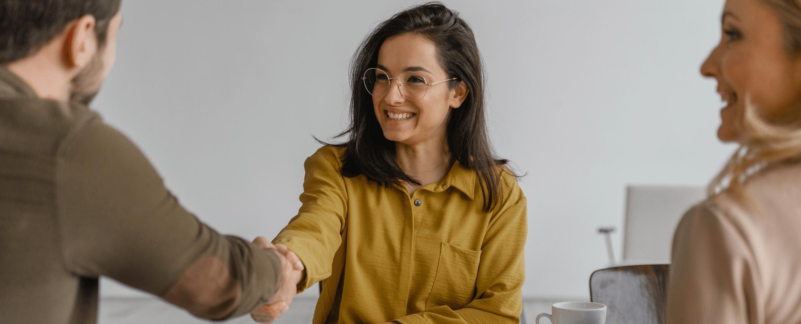 Jeune femme souriante qui serre la main à un manager